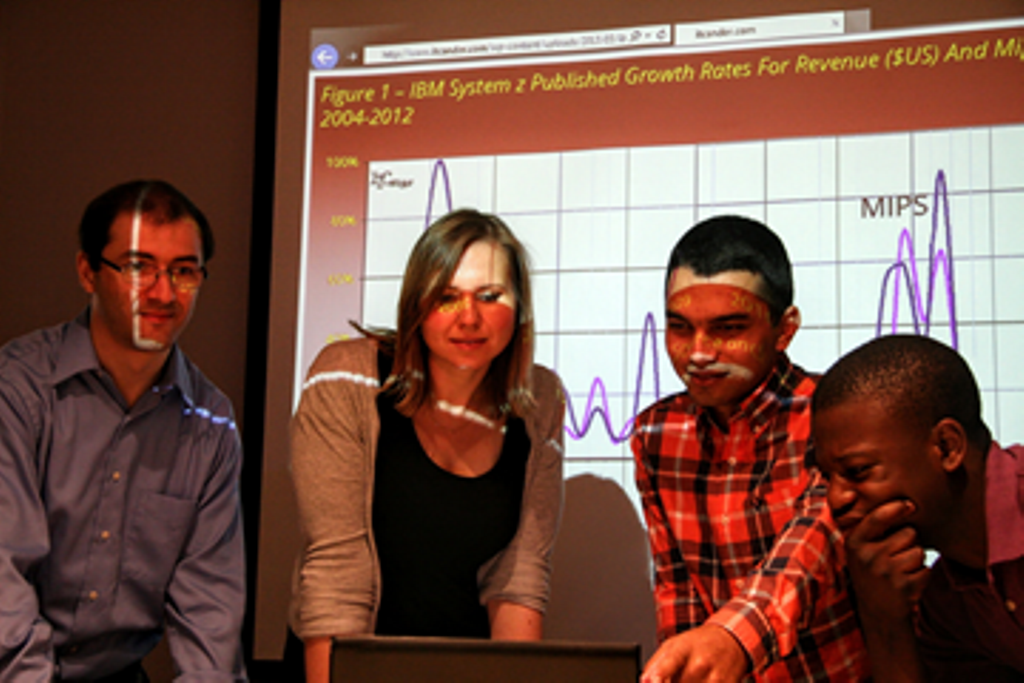 Four individuals staring at the screen of laptop. They are standing in front of a projection of graphics on the wall.