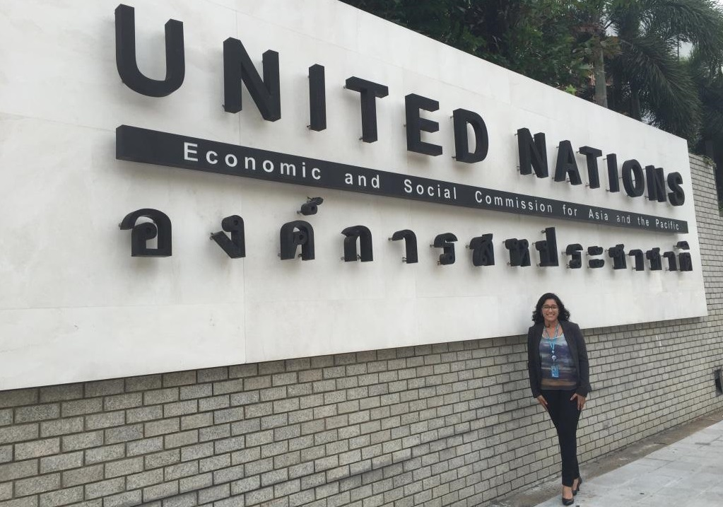 "A woman stands beside a brick wall with a large English-Thai bilingual sign that says ""United Nations Economic and Social Commission for Asia and the Pacific."""