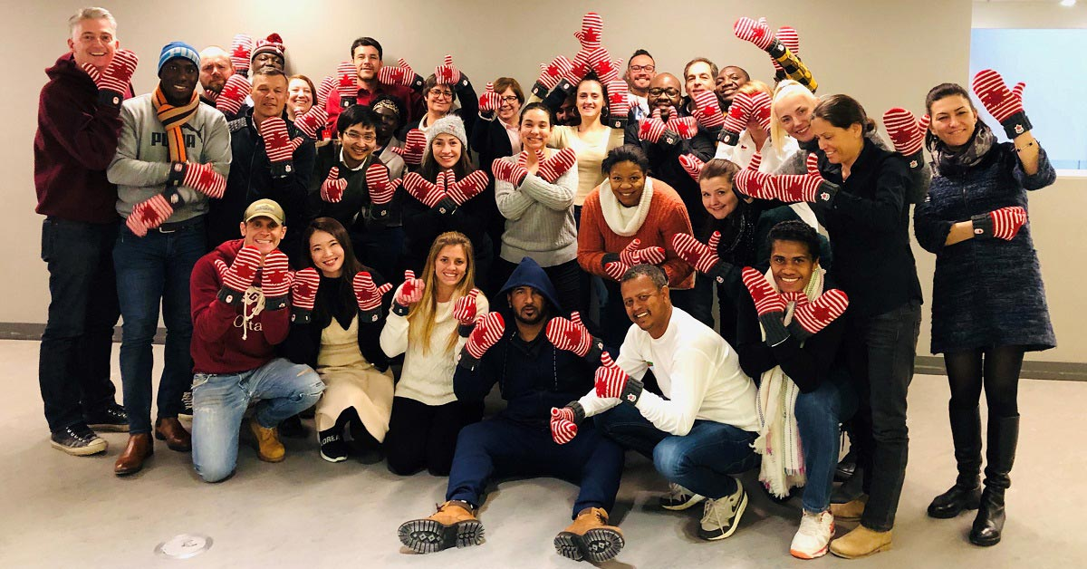 Three dozen smiling people gather for a group photo wearing mittens emblazoned with Canadian flags.