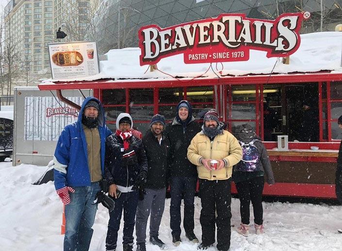 Cinq hommes en vêtements d'hiver devant un kiosque de queues de castor sur le canal Rideau.
