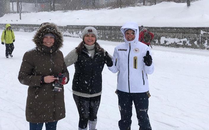 Trois femmes joyeuses sur le canal Rideau pendant une averse de neige.