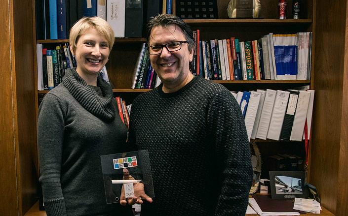 Milena Parent et Benoît Séguin, debout devant une bibliothèque, tiennent un prix MEMOS.