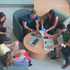 A group of students seen from above. They are sitting at a table with books and laptops.