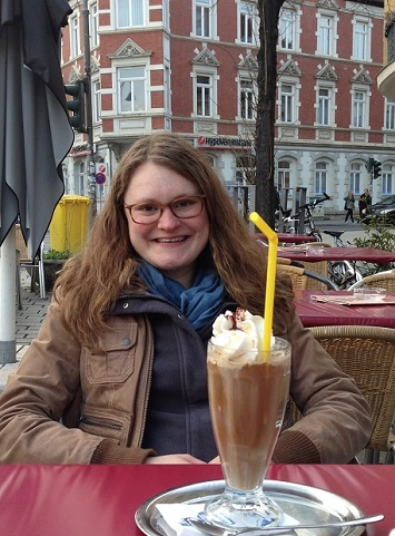 A young woman, smiling and wearing glasses, sits at an outdoor café with a tall beverage topped with whipped cream on the table in front of her.