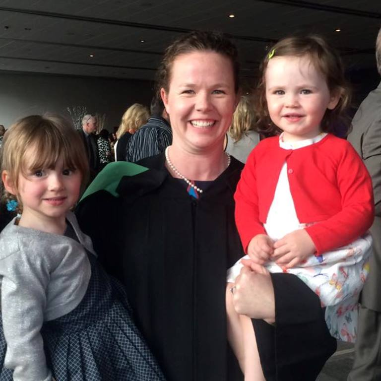 A smiling Michelle Whitty at the graduation reception wearing her graduation gown and hood and holding her two young daughters, one in each arm