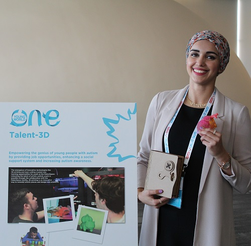 Midia Shikh Hassan stands beside a poster board describing her business idea.