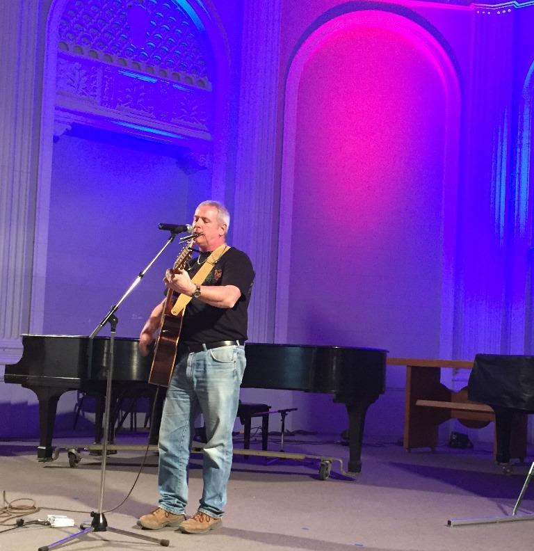 Un homme debout sur scène devant un micro, joue à la guitare.