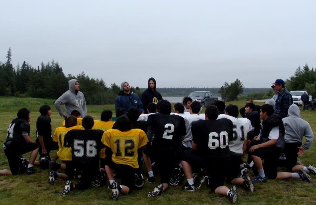 Des jeunes en uniforme de football s'agenouillent devant leurs entraîneurs.