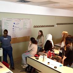 Des élèves entourent une enseignante en classe.