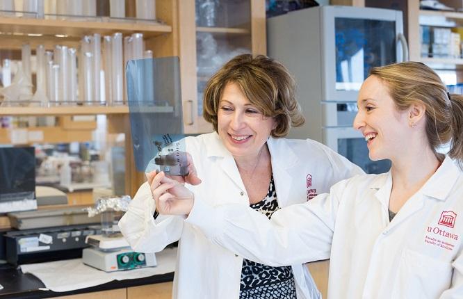 Dans un laboratoire de recherche, Mona Nemer examine des résultats de tests en compagnie d'une étudiante.