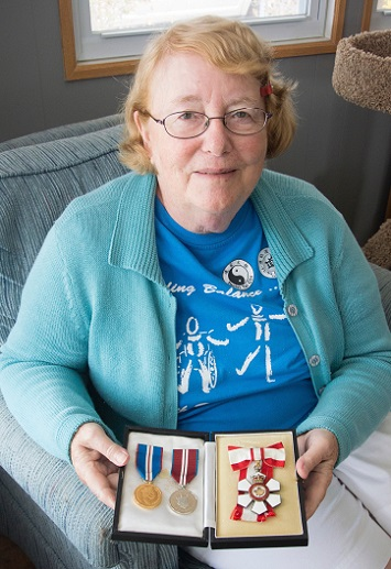 Monique Frize sits in her living room holding three medals.