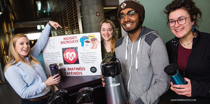 Three women and a man hold reusable coffee mugs, one woman is pointing at a Muggy Mondays sign.