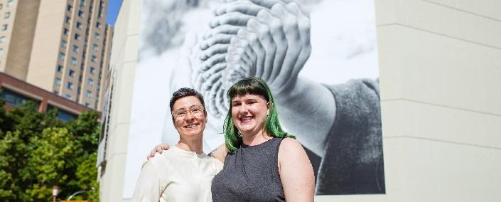 Deux femmes souriant devant la murale.