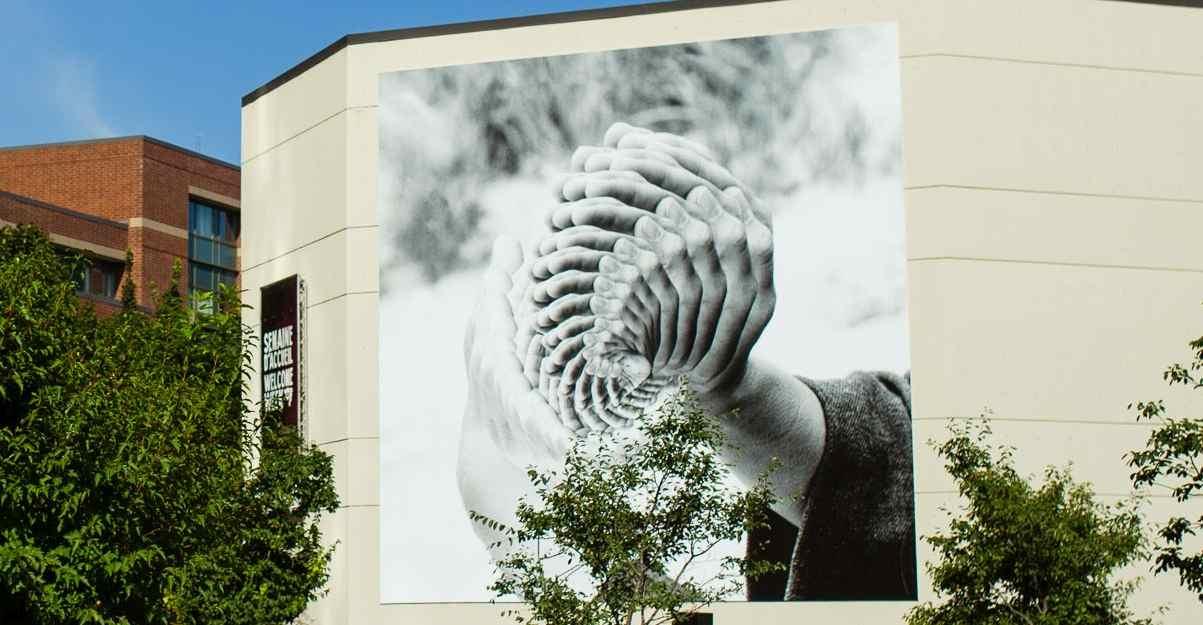Immense toile accrochée sur le mur extérieur d'un immeuble représentant des mains, reproduites en superposition.