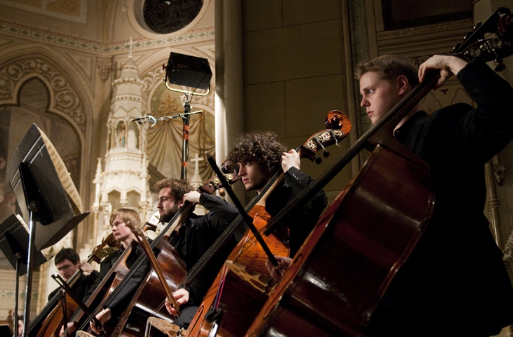 Five men at in an orchestra playing the cello