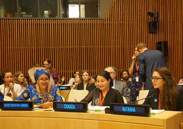 Natasha Harris-Harb sits beside Maryam Monsef in a UN meeting room.
