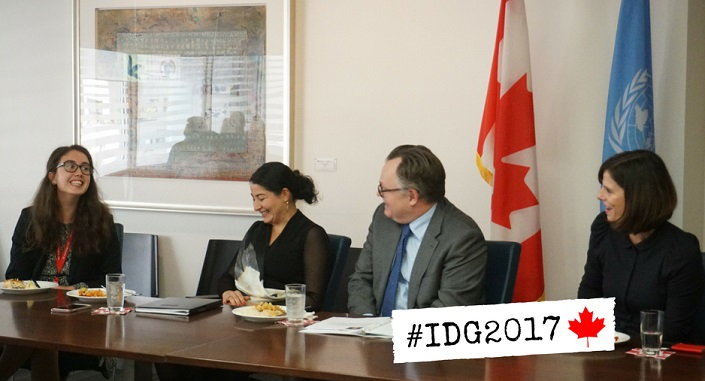 Three women and a man sit at a meeting room table, with the flags of Canada and the United Nations behind them.