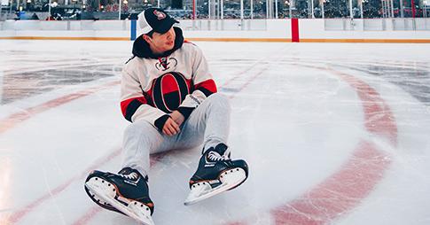 Nick Le, patins aux pieds, assis sur la glace de la patinoire de la Colline du Parlement.