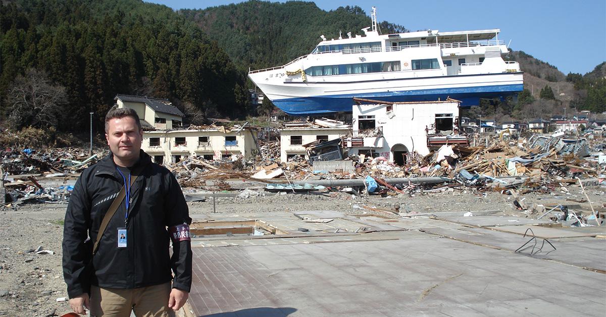 Le professeur Ioan Nestor se tient devant un bâtiment et un navire ravagés par le tsunami survenu en 2011 dans la région de Tōhoku au Japon.