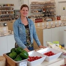 Une jeune femme souriante se tient debout dans une épicerie, derrière un comptoir rempli de fruits et légumes.