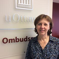 La nouvelle ombudsman de l'Université d'Ottawa, Martine Conway, pose à l'entrée de son bureau devant une enseigne sur laquelle est écrit «uOttawa | Ombudsman».