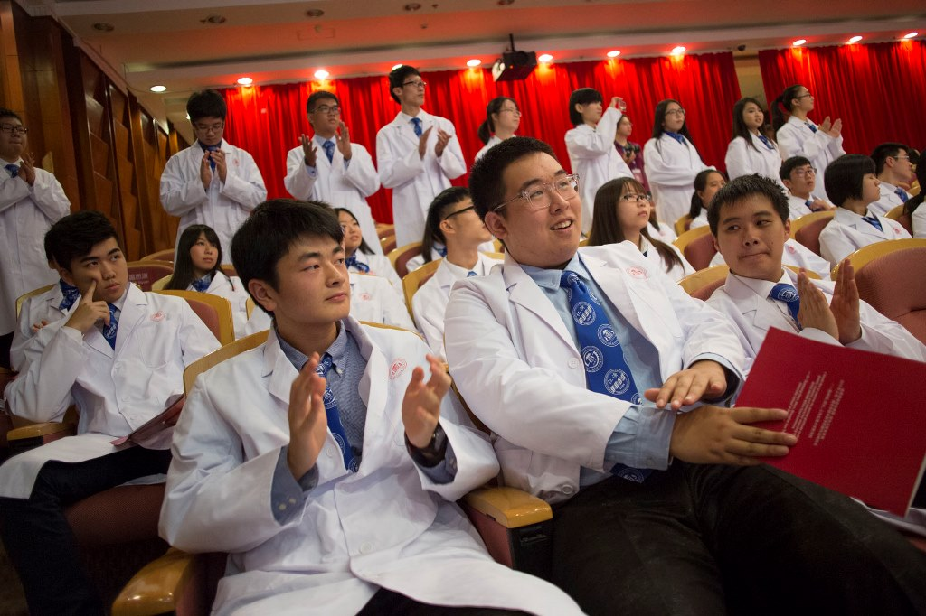 Students wearing white coats sitting and clapping in an auditorium.