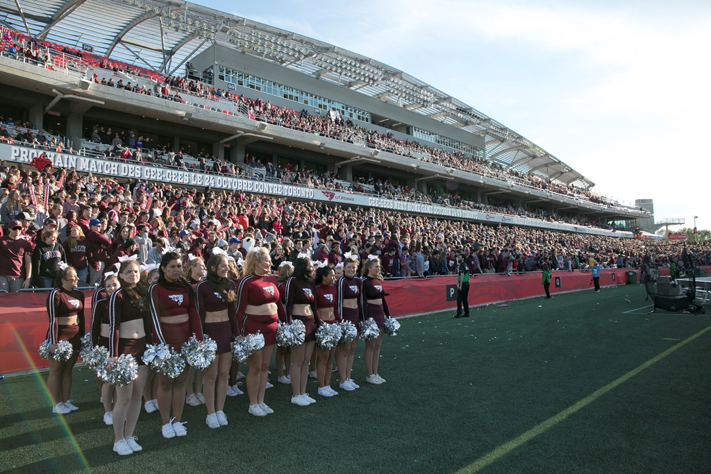 Stadium with three levels of stands filled with people. Standing in the foreground is a group of female cheerleaders holding pompoms.