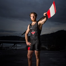 Andrew Todd wearing lycra shorts and sleeveless shirt with an oar slung across his shoulder