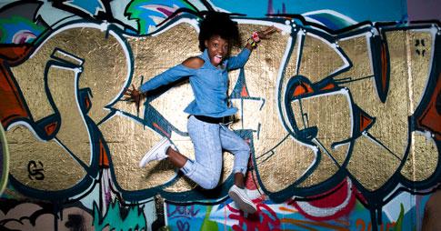 Pearline Barrett-Fraser saute en dansant devant un mur de graffitis colorés