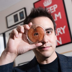 Man holding up a petri dish containing a slice of apple