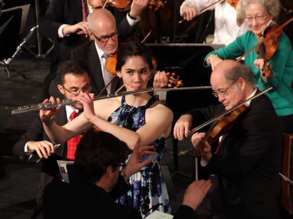 A woman playing the flute during a concert.