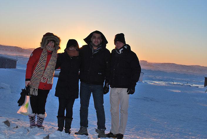 Quatre personnes bien enveloppées dans des vêtements d'hiver sont regroupées debout devant la toundra arctique.