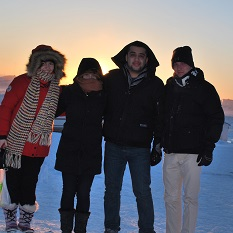 Four students dressed in winter clothing stand in the foreground with the Arctic tundra in the background.