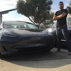 A man standing next to a Tesla sedan