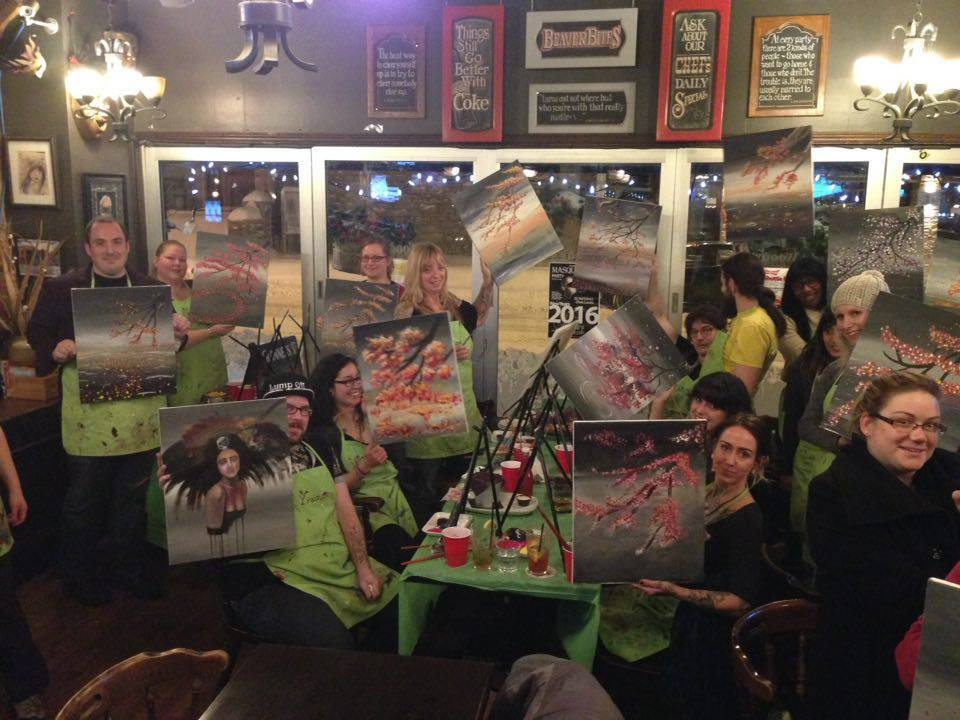 A group of people displaying finished paintings that vary slightly.