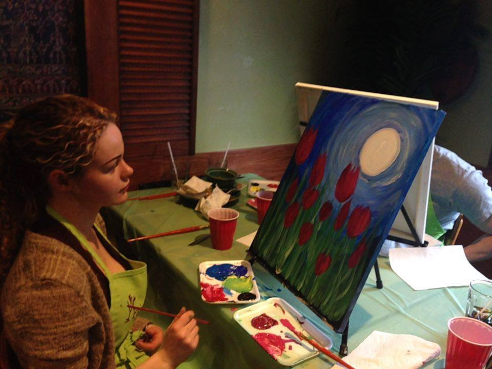 A woman sitting in front of a canvas gazes at her painting of tall tulips against a moonlit sky.