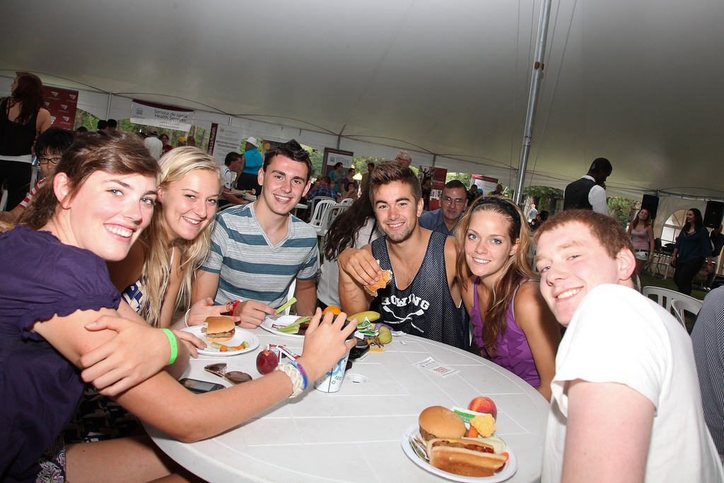 Students enjoying a picnic under a white tent
