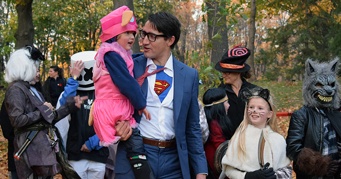 Children and adults in Halloween costumes, with a Superman logo peeking out from behind the prime minister's partially unbuttoned shirt.