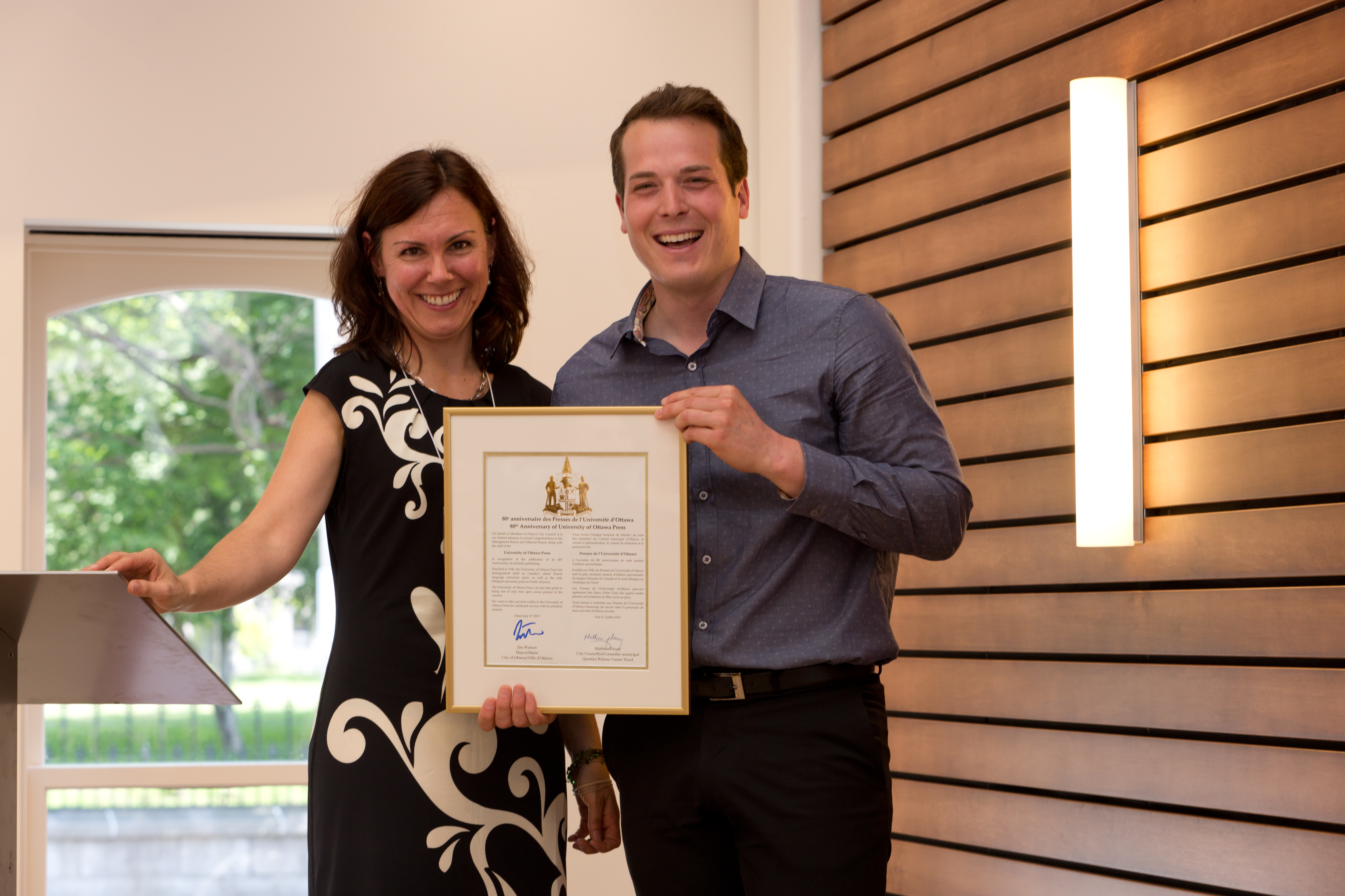 UOP director Lara Mainville receives a plaque from Ottawa City Councillor Mathieu Fleury