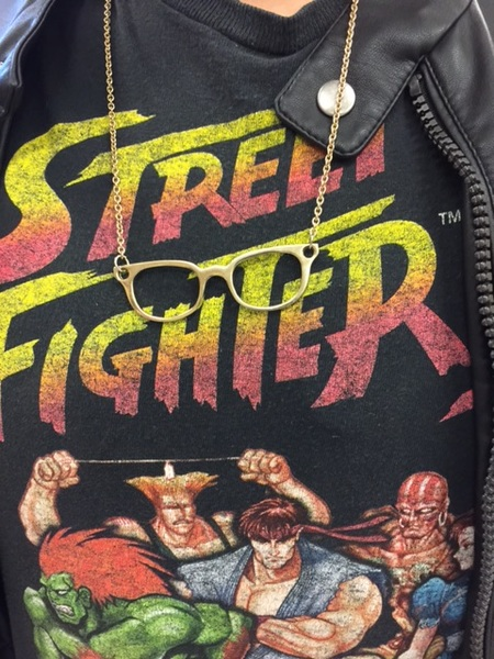 A necklace of miniature eyeglasses on a Street Fighter T-Shirt.