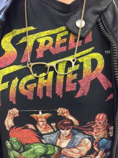 Un collier de lunettes miniatures sur un T-shirt de Street Fighter.