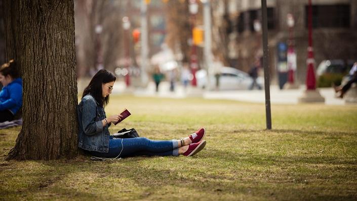 Une étudiante lit un livre, assise contre un arbre sur la pelouse devant le pavillon Tabaret.