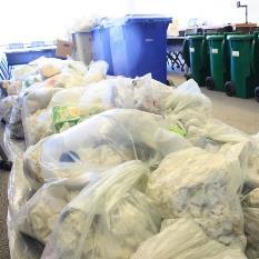 Des sacs de déchets à recycler empilés à côté d'une rangée de bacs à recyclage.