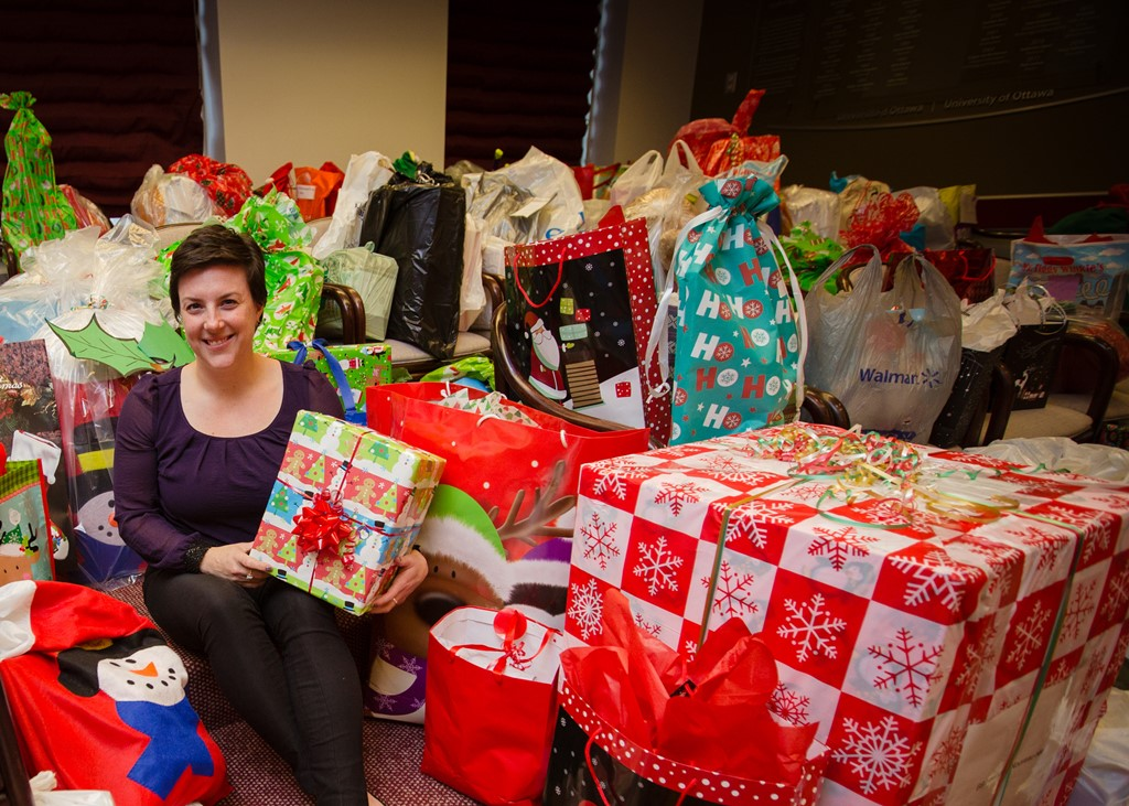 Anne-Marie Lacroix sits surrounded by many giftwrapped boxes and bags of gifts.