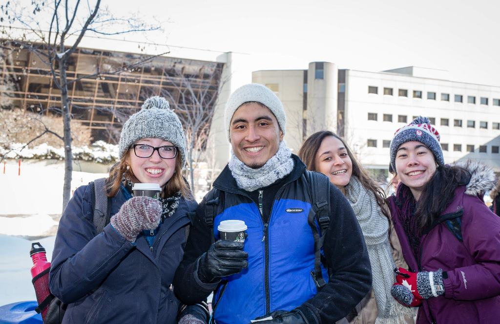 Three girls and a guy bundled in warm clothes for the wintery cold.