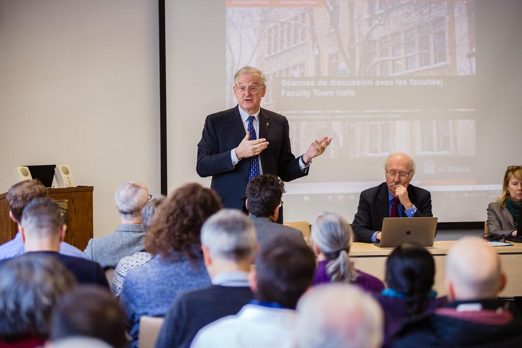 Jacques Frémont prononce un discours debout devant un groupe de personnes, tandis que David Graham est assis non loin avec un ordinateur portable.