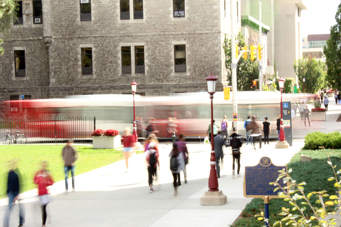 An OC Transpo bus travels along a campus street while pedestrians wait to cross.