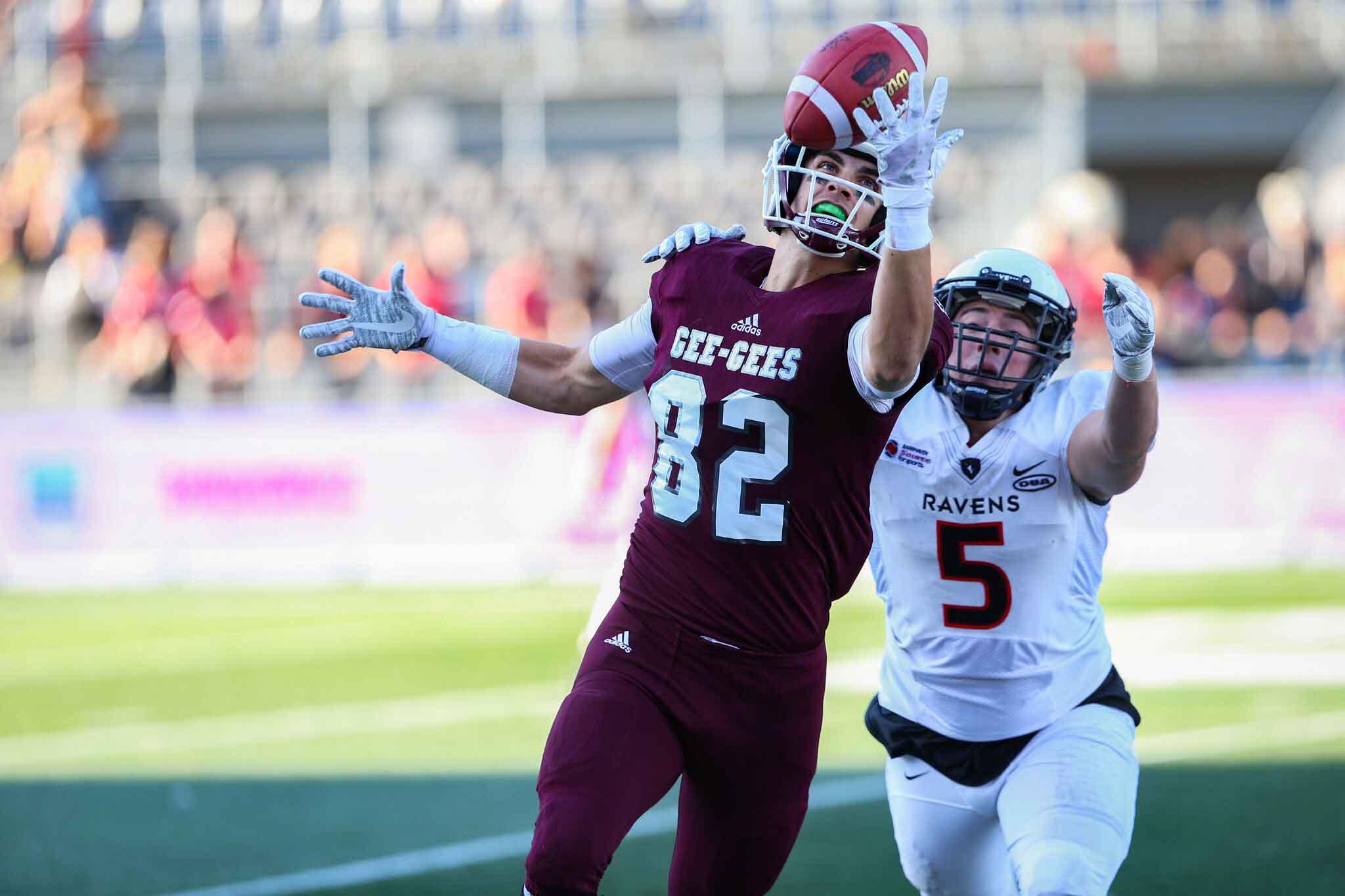 Un joueur de football de l'Université d'Ottawa attrape le ballon d'une seule main.