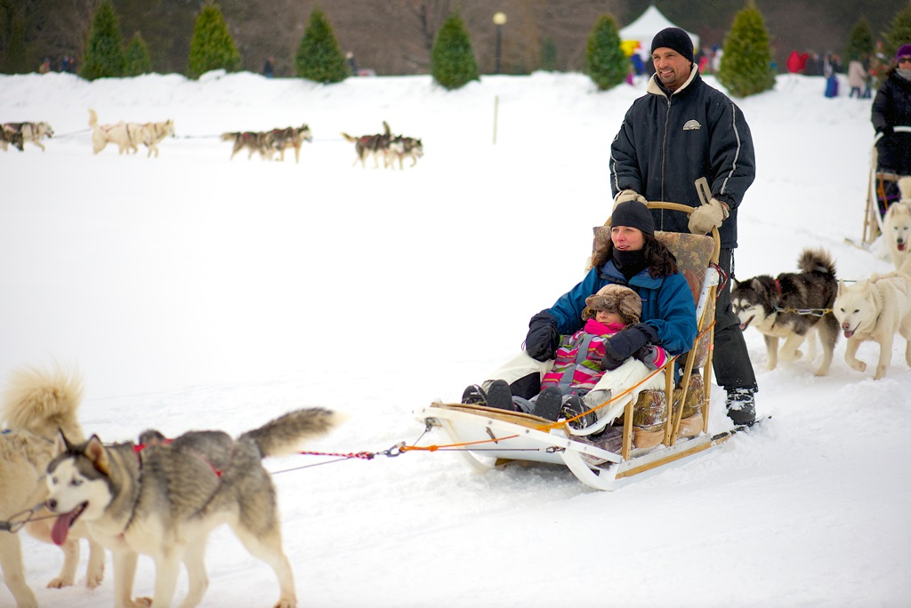 A woman and child sitting in a dog sled with a man standing on the runners, being pulled by a team of dogs.