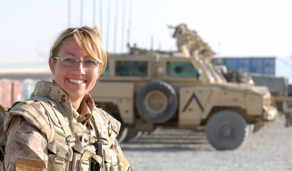 Hélène LeScelleur, souriante, en tenue de combat. Derrière elle, un véhicule militaire.